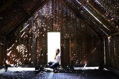 The girl sits in the doorway. Wooden barn with beautiful sun highlights. Art object in the art park of Nikola Lenivets stock image