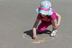 Girl sits and draws with chalk on asphalt Apple. stock image