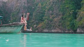 Girl sits on the edge of the boat. In paradise place stock video footage