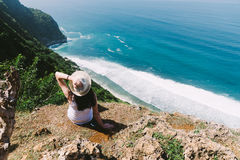 A girl sits on the edge of a cliff.Bali. Royalty Free Stock Photos