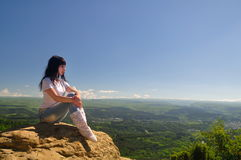 A girl sits on the edge of a cliff and looking into the distance Royalty Free Stock Images
