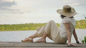 Girl sits on the edge of an old wooden pier berth dock. Girl in a hat sits on the edge of an old wooden pier berth dock near the lake pond. Rear view. Rest relax stock video footage