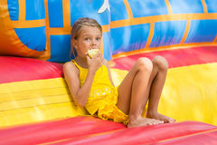 Girl sits at entrance to an inflatable trampoline and eating an apple Stock Photo