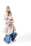 Girl sits on father shoulders, mother supports her royalty free stock photo