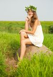 Girl sits on field stone Royalty Free Stock Images
