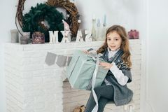 A girl sits at the fireplace and holds a box with a gift in her hands. Holiday time. A girl sits at the fireplace and holds a box with a gift in her hands Stock Photos