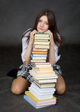 Girl sits on a floor embracing big pile of books Stock Photography