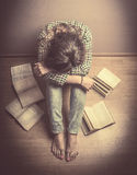 Girl sits on the floor with his head resting on his knees around it laid open the book, Study tired, student, retro  toning Royalty Free Stock Image