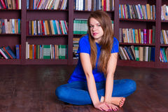 Girl sits on the floor in library Royalty Free Stock Photos