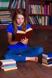 Girl sits on the floor in library Stock Photo