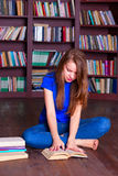 Girl sits on floor in the library Royalty Free Stock Photos