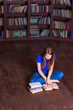 Girl sits on floor in the library Stock Photography