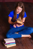 Girl sits on floor in the library Stock Image