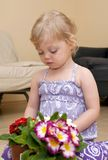 Girl sits on the floor and plays with flower Stock Photography