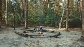 A girl sits in the forest reading a book. The girl sits on a log next to the fire and reads a book, aerial view,