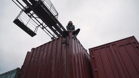 The girl sits on a freight container.  stock video