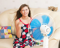 The girl sits in front of the fan Royalty Free Stock Photo