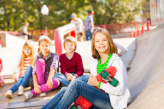 Girl sits in front with skateboard and other kids Stock Photos