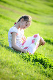 Girl sits on a grass. Happy girl sits on a grass Stock Photo