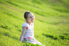 Girl sits on a grass Stock Photo