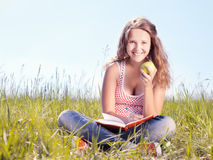 Girl with an apple. Girl sits on a grass and eats a green apple stock image