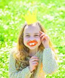 Girl sits on grass at grassplot, green background. Child posing with cardboard smiling lips and crown for photo session. At meadow. Humour queen concept. Girl stock photography