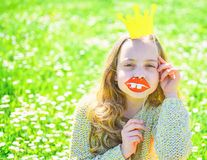 Girl sits on grass at grassplot, green background. Child posing with cardboard smiling lips and crown for photo session. At meadow. Girl on cheerful face spend royalty free stock image