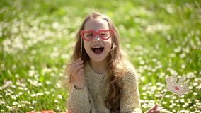Girl sits on grass at grassplot, green background. Child girl spend leisure outdoors. Best holiday concept. Child posing. With crown and eyeglasses photo booth stock video