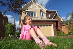 Girl sits on grass and looks into distance Stock Photos