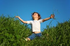 Girl sits in grass and looks upwards Royalty Free Stock Photography
