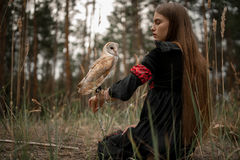 Girl sits on grass with owl on her hand in forest. Stock Photography