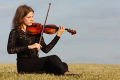 Girl sits on grass and plays violin against  sky Royalty Free Stock Images