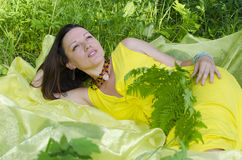 Girl sits on a grass in the summer wood Stock Images