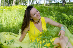 Girl sits on a grass in the summer wood Royalty Free Stock Photos