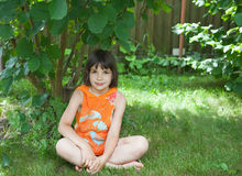 The girl sits on a grass under a bush. The girl in an orange vest sits on a grass under a bush Royalty Free Stock Images