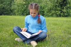 Girl sits on green field and reads book Stock Photos