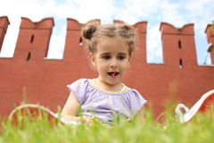Girl in sits on the green grass near old brick wall. Little girl in sits on the green grass near old brick wall and made interesting forms tongue royalty free stock photography