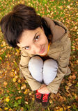 Girl sits on ground. Beautiful dark-haired woman sits on earth covered with autumn fallen leaves Royalty Free Stock Photos
