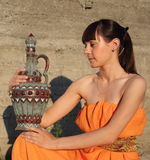 The girl sits and has control over a jug Stock Photography