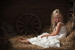 Girl sits on hay in the barn Royalty Free Stock Photo
