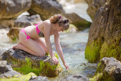 Girl sits on heels on rock and touches sea water looking down Royalty Free Stock Images