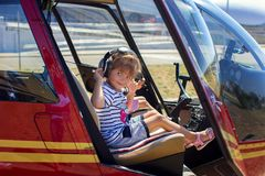 The girl sits at a helicopter steering wheel. In earphones Royalty Free Stock Image
