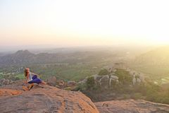 A girl sits with her back on the top of the mountain and looks at the sunset at Hampi and welcomes the sun. Meditation, harmony,. Alone with nature, silence royalty free stock photos