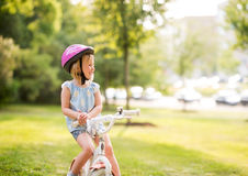 A girl sits on her bicycle in a city park Royalty Free Stock Image