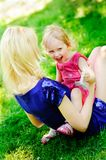 Girl sits on her mother's knees on a green lawn Stock Image