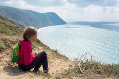 The girl sits on high bank and looks at the sea Royalty Free Stock Photo