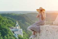 Girl sits on hill with camera. Forest and temple below Stock Photo