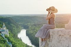 Girl sits on hill with camera. Forest, temple and river below Royalty Free Stock Photos