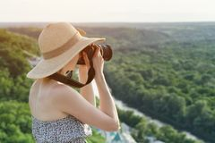 Girl sits on hill and takes pictures against the background of a Stock Images