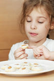 Girl sits and holds cookies with almonds Stock Images